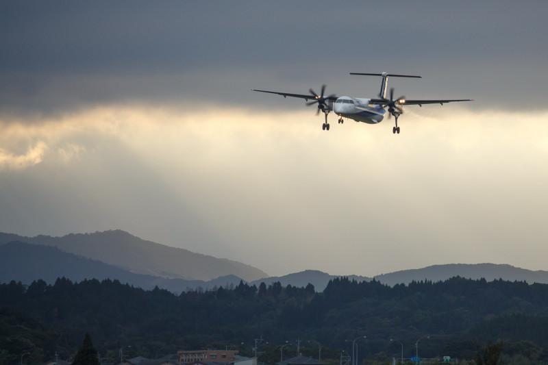 低い雲をくぐり抜けて着陸する飛行機ボンバルディア機