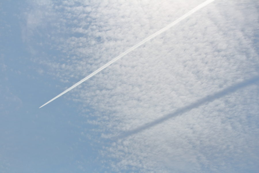 宮崎空港上空を通過する飛行機雲の影がその下の雲に映し出された