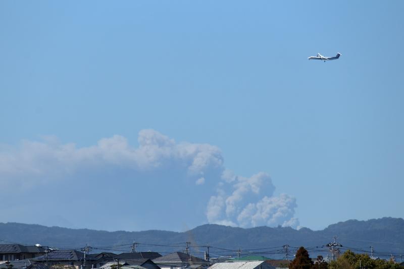 新燃岳と宮崎空港に着陸予定のボンバルディア飛行機