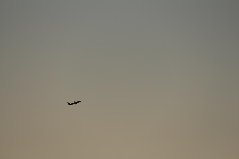 宮崎空港離陸後西向かったJAL機がライトターンじわずかの光でキラリする飛行機