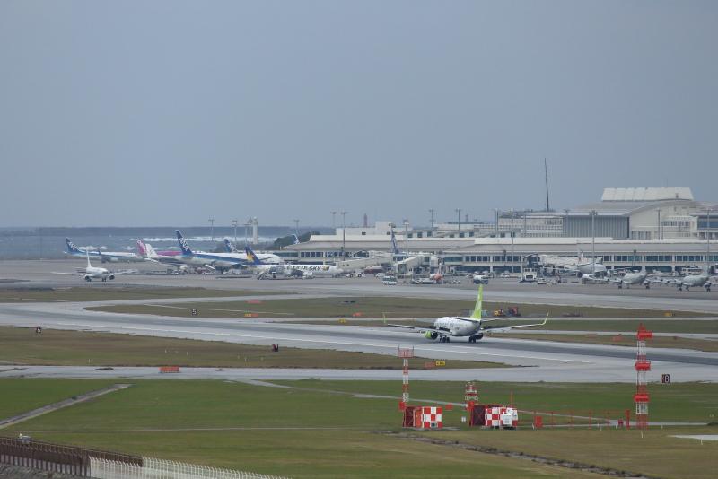 那覇空港に着陸する飛行機を島から眺めることができる。